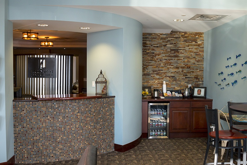 Lakewinds Dental Centre front office area with amenities like coffee, a refrigerator with drinks, and a seating area