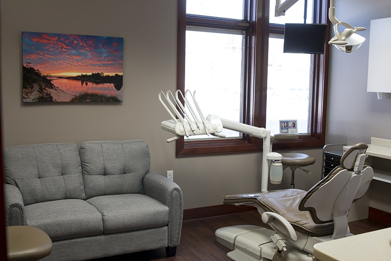 Lakewinds Dental Centre examination room complete with a sunset portrait on the wall and a couch to relax on